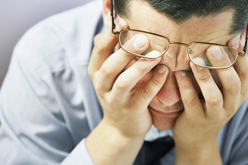 stressed employee covering his face