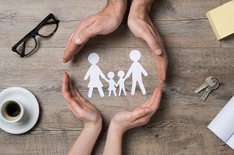 hands protecting paper cut-out of family